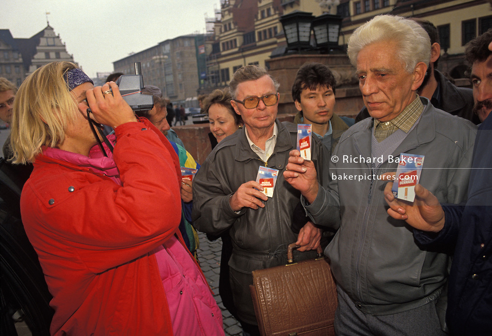 A year after the fall of the Berlin Wall and the end of the Communist Eastern Bloc, a cigarette brand marketing lady  hands out promos for 'Prince of Denmark' and photographs unhappy-looking former east Germans with a Polaroid camera in Leipzig's town square, on 4th November 1990, in Leipzig, Germany.