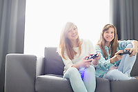 Sisters playing video games on sofa