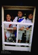 Girls watch passing parade from window wearing red and blue colors of Padstow's two May Day hobby horses; Cornwall, England.