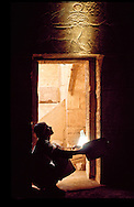 """Artifacts on tomb interior at Deir El-Medina """"Thebes"""" being lit by use of mirrors to reflect the sunlight deep into the tomb.  Luxor, Egypt"""