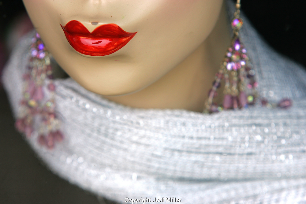 the red lips of a mannequin wearing a scarf and earrings.