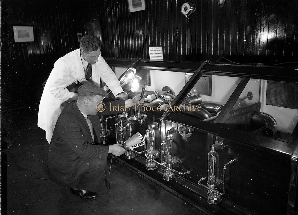 16/12/1959<br /> 12/16/1959<br /> 16 December 1959<br /> <br /> Mr. Frank O' Brien Controls the Spirt as it comes from the vat into the spirt safe in the control room watched by distiller Mr. D. Cotter