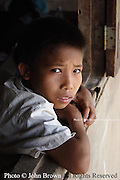 A student at The Ban Buamlao Primary School in Ban Baumlao, Laos, pauses to lean on a schoolhouse windowsill before returning to his village to eat lunch. The impoverished school lacks basic learning supplies such as books, paper, and recreational equipment.