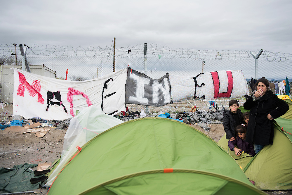 A family of refugees standing right next to the fence build by the FYR Macedonian Police and a banner writing &ldquo;Made in EU&rdquo; Transit camp of Idomeni, Greece. <br /> <br /> Thousands of refugees are stranded in Idomeni unable to cross the border. The facilities are stretched to the limit and the conditions are appalling.