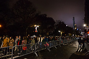 New York, NY – 27 November 2019. Thousands of spectators packed the streets around the American Museum of Natural History to see the inflation area for the balloons for Macy's Thanksgiving Day Parade. Spectators on Central Park West queue behind police barricades to get in.