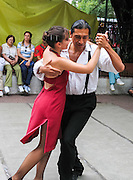 A man in white shirt and black pants dances tango with a woman in a red dress, as a free demonstration in Dorrego Square, in San Telmo barrio of Buenos Aires, Argentina, South America.