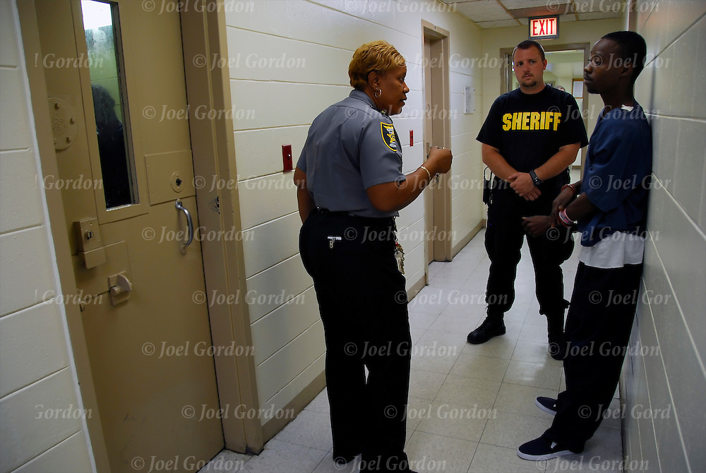 High ranking female African American correction officer Major Paula Carter conducting daily site tour of jail interacting with officers and inmates