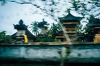 A blurred image of a temple from a bicycle in Ubud, Bali, Indonesia.