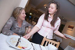 Waitress chatting to customer whilst collecting empty plates at a Polish restaurant,