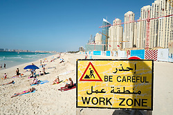 Construction site sign next to each and high-rise modern apartment buildings near Marina at New Dubai in United Arab Emirates