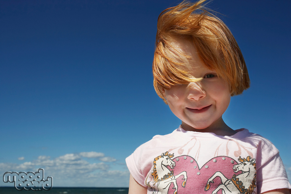 Portrait of ginger haired girl (5-6) against blue sky
