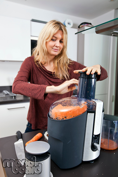 Woman juicing carrots at kitchen counter