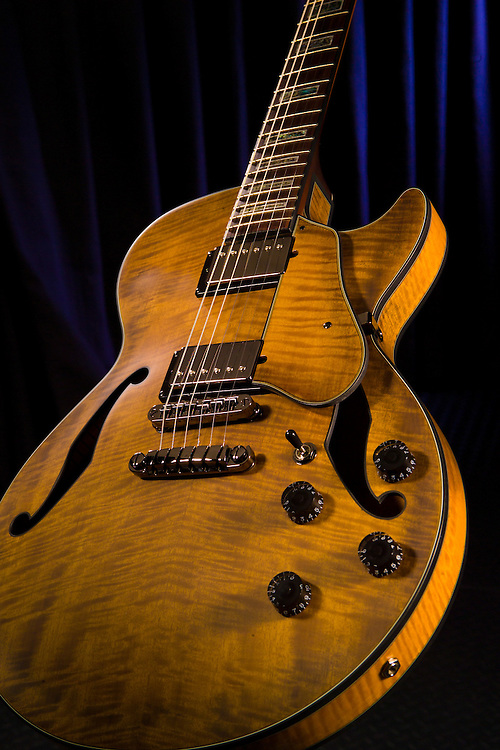 Beautiful wood grained electric Ibanez guitar with a dark blue curtain background.