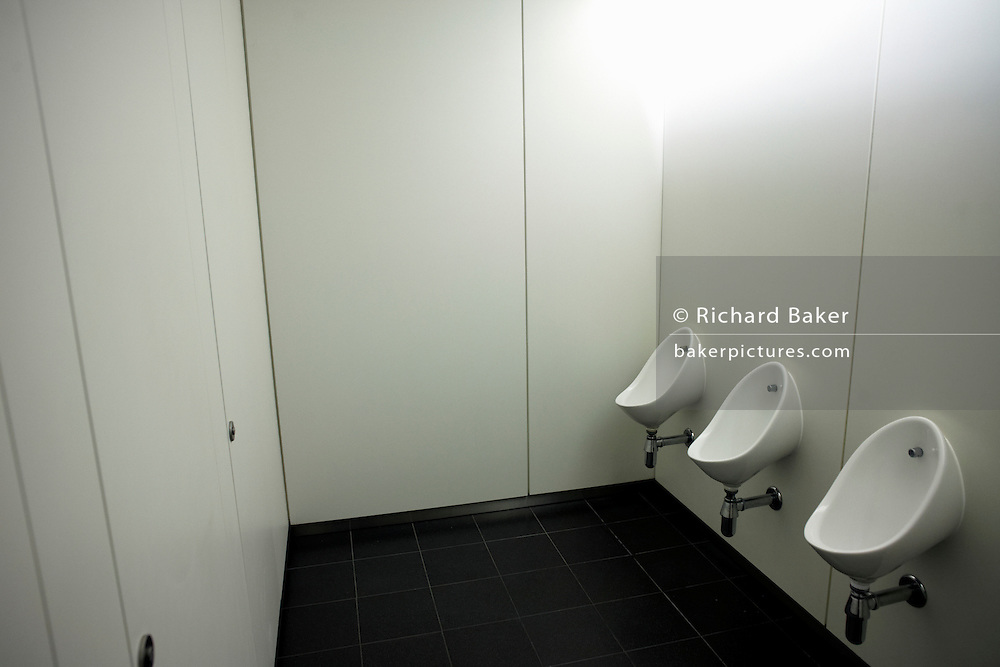 Three clean office urinal toilets at an auditing company's London headquarters.