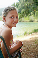 Girl (7-9) sitting on deck chair by lake.