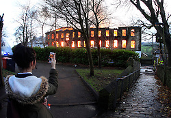 © Paul Thompson Licensed to London News Pictures. 19/11/2015. Thornton, Bradford. Girl filming a fire at Prospect Mill in Thornton Village on her phone. Photo credit : Paul Thompson/LNP
