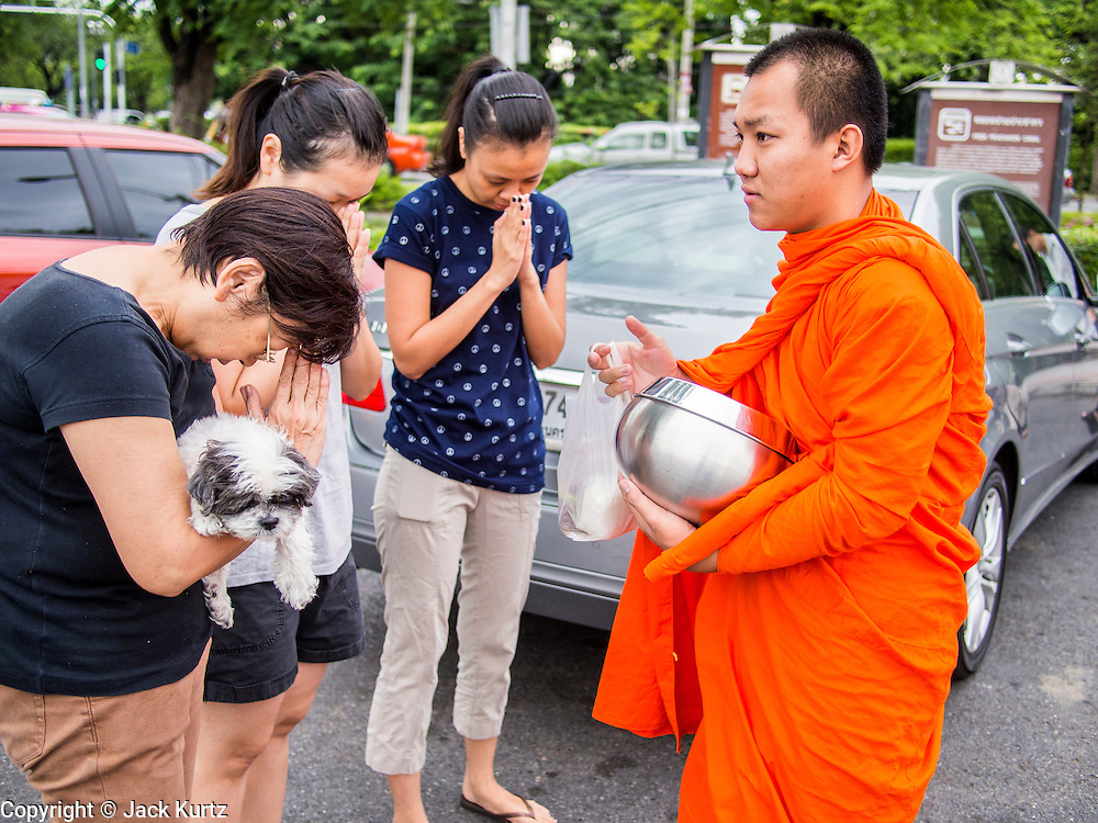 "21 JULY 2013 - BANGKOK, THAILAND:  Women, one holding a dog, pray while a monk blesses them after they made merit at Wat Benchamabophit on the first day of Vassa, the three-month annual retreat observed by Theravada monks and nuns. On the first day of Vassa (or Buddhist Lent) many Buddhists visit their temples to ""make merit."" During Vassa, monks and nuns remain inside monasteries and temple grounds, devoting their time to intensive meditation and study. Laypeople support the monastic sangha by bringing food, candles and other offerings to temples. Laypeople also often observe Vassa by giving up something, such as smoking or eating meat. For this reason, westerners sometimes call Vassa the ""Buddhist Lent.""       PHOTO BY JACK KURTZ"