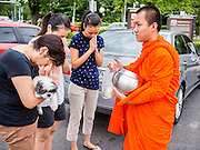 """21 JULY 2013 - BANGKOK, THAILAND:  Women, one holding a dog, pray while a monk blesses them after they made merit at Wat Benchamabophit on the first day of Vassa, the three-month annual retreat observed by Theravada monks and nuns. On the first day of Vassa (or Buddhist Lent) many Buddhists visit their temples to """"make merit."""" During Vassa, monks and nuns remain inside monasteries and temple grounds, devoting their time to intensive meditation and study. Laypeople support the monastic sangha by bringing food, candles and other offerings to temples. Laypeople also often observe Vassa by giving up something, such as smoking or eating meat. For this reason, westerners sometimes call Vassa the """"Buddhist Lent.""""       PHOTO BY JACK KURTZ"""