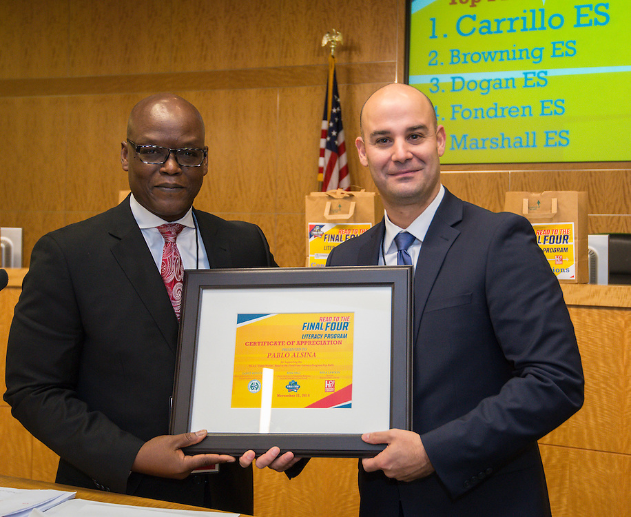 Lawrence Allen, left, presents a recognition to Pablo Alsina, right, during the reveal of the 32 finalists in the Houston ISD NCAA Read to the Final Four, November 11, 2015.