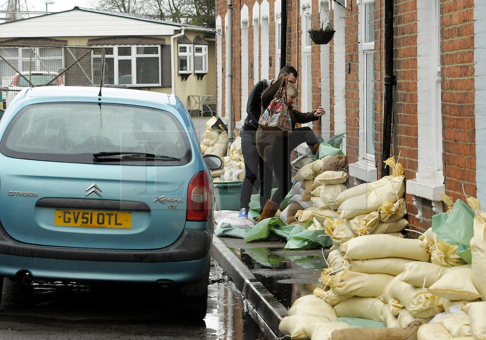 © Licensed to London News Pictures. 14/02/2014; Gloucester, UK.  Residents have to climb over sandbag defences in Alney Terrace in Alney Island which is subject to a Severe Flood Warning, threatened by rising water levels from the nearby river Severn.  The residents have been given sandbags by Gloucestershire Council.<br /> Photo credit: Simon Chapman/LNP