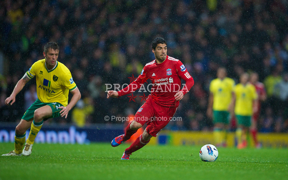 NORWICH, ENGLAND - Saturday, April 28, 2012: Liverpool's Luis Alberto Suarez Diaz looks up to see the Norwich City goalkeeper off his line on his way to scoring the third goal of his hat-trick during the Premiership match at Carrow Road. (Pic by David Rawcliffe/Propaganda)