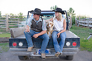 Western American cowboy couple sit on the back of a pick up with their dog.