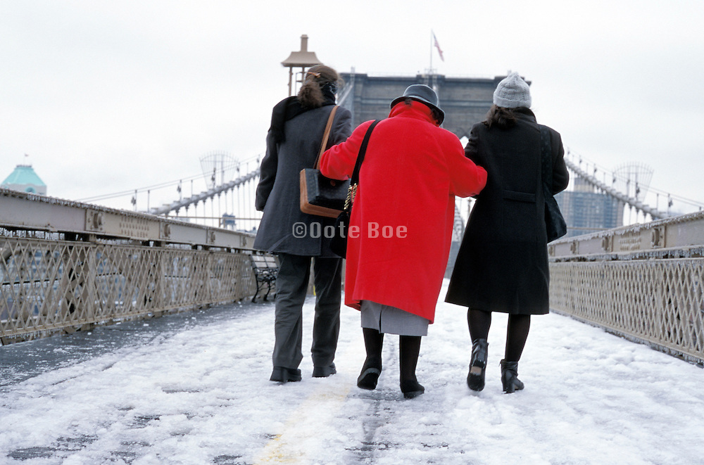 2 young women helping an elderly woman walking over the Brooklyn Bridge