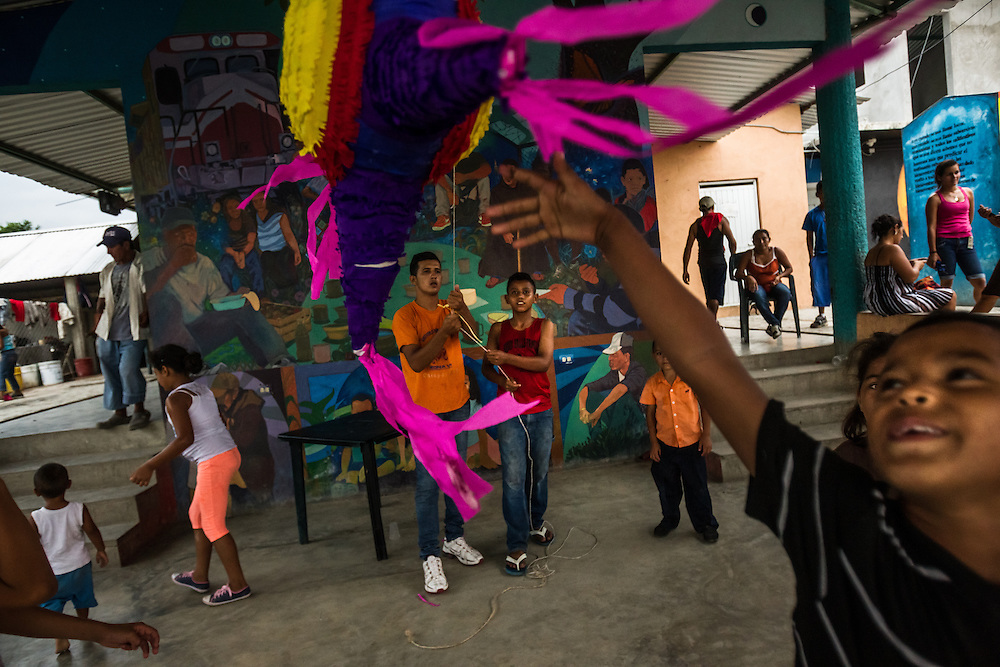 TENOSIQUE, MEXICO - MAY 29, 2014:  Children play with a pinata at the 72 migrant shelter in Tenosique, where  Catholic priests and other volunteers provide mats for migrants to sleep on, second-hand clothes, meals, basic medical treatment, and help applying for immigration visas and refugee status to people traveling north. The shelter, which traditionally has been visited by men between the ages of 15-35, has been overrun by women and children in recent months, more than double the amount -- consequential of a recent boom of minors headed to the United States from Central America. PHOTO: Meridith Kohut for The New York Times