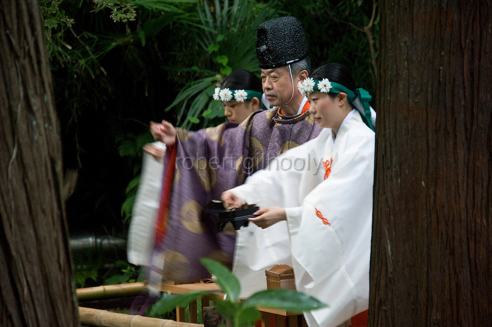 """A priest and maiko attendants release bell crickets that have been dedicated to the shrine """"kami"""" (gods) during the suzumushi-hojosai rite that marks the end of the  3-day Reitaisai festival in Kamakura, Japan on  14 Sept. 2012.  The ritual is observed in order to recognize the preciousness of life, releasing the insects by a pond inside the shrine grounds. Photographer: Robert Gilhooly."""