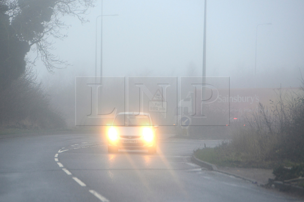 © Licensed to London News Pictures. 26/12/2013. Oxfordshire, UK A car exits a roundabout in heavy fog. Foggy driving conditions on the M40 in Oxfordshire today. Photo credit : Stephen Simpson/LNP