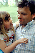Father age 42 holding 7 year old daughter.  Clitherall Minnesota USA