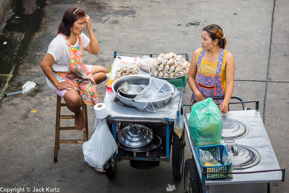"24 AUGUST 2013 - BANGKOK, THAILAND: Food cart operators wait for customers on a street in Bangkok. Thailand entered a ""technical"" recession this month after the economy shrank by 0.3% in the second quarter of the year. The 0.3% contraction in gross domestic product between April and June followed a previous fall of 1.7% during the first quarter of 2013. The contraction is being blamed on a drop in demand for exports, a drop in domestic demand and a loss of consumer confidence. At the same time, the value of the Thai Baht against the US Dollar has dropped significantly, from a high of about 28Baht to $1 in April to 32THB to 1USD in August.    PHOTO BY JACK KURTZ"