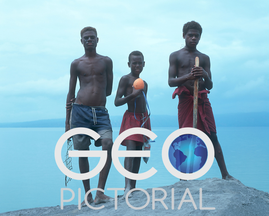 Three boys from Matupit Island fish in the sulphrous sea under the shadow of Mount Tuvurvur..Matupit, New Britain Province, Papua New Guinea;
