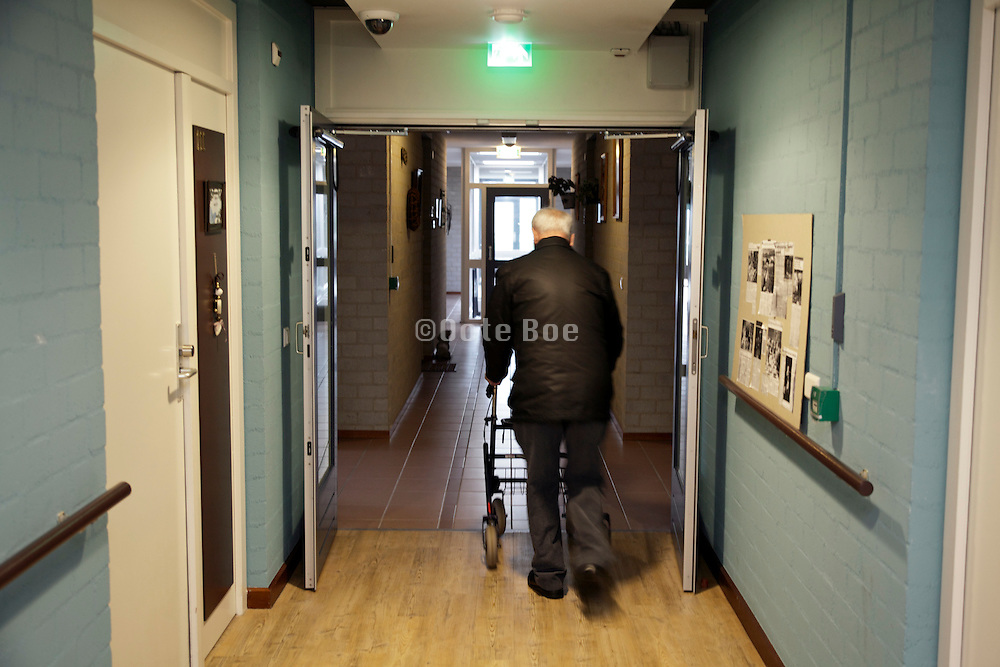 senior man walking with a walker in the hall of a retirement home
