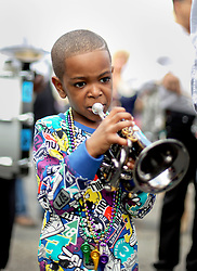 31 January 2016. New Orleans, Louisiana.<br /> Donte Allen (5 yrs old) with the Treme Brass Band at the Mardi Gras Dog Parade. The Mystic Krewe of Barkus winds its way around the French Quarter with dogs and their owners dressed up for this year's theme, 'From the Doghouse to the Whitehouse.' <br /> Photo©; Charlie Varley/varleypix.com