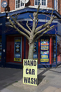 Nearby Hand Car Wash business sign leaning against an urban tree in south London.