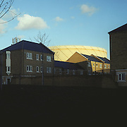 Sunlit Victorian Gasometer towering over suburban housing. Poplar, East London. 12.2003. UK