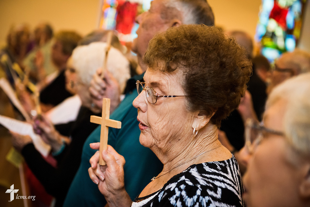 "Elaine Spenner, a parishioner at Trinity Lutheran Church in Hoyleton, Ill., lifts high a cross constructed from the wood of the former steeple of St. John's Lutheran Church, which was damaged nearly two years ago from a tornado, during a ""Day of Thanksgiving and Rededication"" at the church on Sunday, August 9, 2015, in New Minden, Ill. LCMS Communications/Erik M. Lunsford"