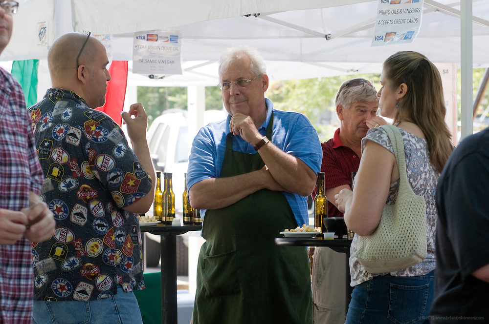 Bob Hundley of Primo Oils and Vinegars gives visitors to their booth at the Douglas Loop Farmers Market a taste of their infused oils Saturday, Aug. 11, 2012 in Louisville, Ky. (Photo by Brian Bohannon).