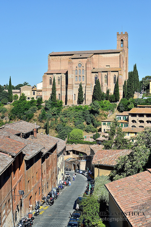 The Basilica of San Domenico, also known as Basilica Cateriniana, is a basilica church in Siena, Tuscany, Italy, one of the most important in the city.The church was begun in 1226-1265, but was enlarged in the 14th century to the Gothic appearance it has now. It is a large edifice built, like many contemporary edifice of the mendicant orders, in bricks, with a lofty bell tower on the left (this was reduced in height after an earthquake in 1798). The interior is on the Egyptian cross plan with a huge nave covered by trusses and with a transept featuring high chapels.<br /> The church contains several relics of St. Catherine of Siena, whose family house is nearby.