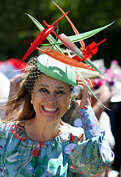 © Licensed to London News Pictures. 21/06/2018. London, UK. A racegoers holds on to her hat at Ladies Day at Royal Ascot at Ascot racecourse in Berkshire, on June 21, 2018. The 5 day showcase event, which is one of the highlights of the racing calendar, has been held at the famous Berkshire course since 1711 and tradition is a hallmark of the meeting. Top hats and tails remain compulsory in parts of the course. Photo credit: Ben Cawthra/LNP