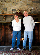 Portrait of Paul & Barb Barnette standing in front of a fireplace warming themselves and smiling broadly.