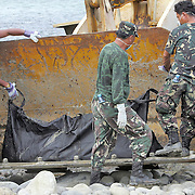 Military removes bodies from a landslide area in the Philippines.