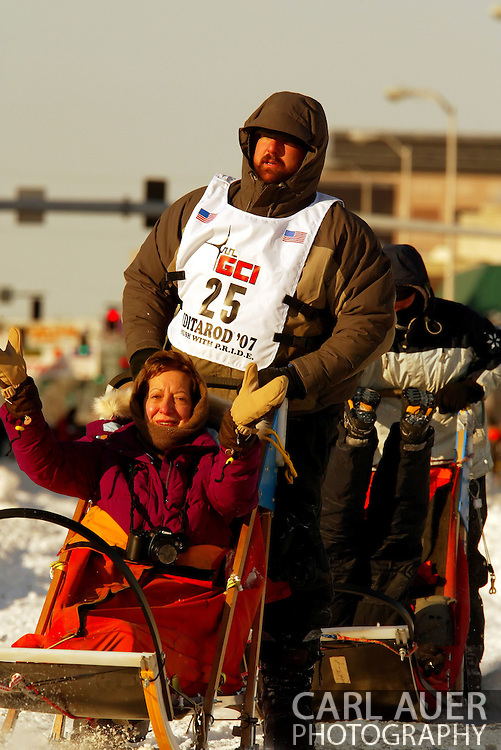 3/3/2007:  Anchorage Alaska -  After untangling a dog, Rookie Richard Hum of Talkeetna, AK gets going again but not before the course worker he asked to help him out could get out of the way of his trailing sled and falls backwards into the second sled during the Ceremonial Start of the 35th Iditarod Sled Dog Race