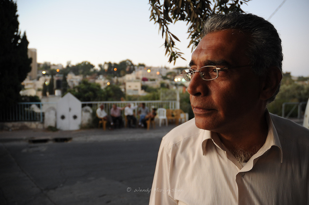 Maher Hannoun looking at his house with some sympathising neighbors on the background. The Hannoun family was evicted out of their house in Sheikh Jarrah earlier last week and now live on the streets across their home that is now being occupied by Jewish settlers. Jerusalem, Israel, 2009