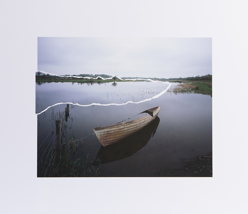 """A Sunken Boat moored to barb wire fence on the shore of the border emerges from the early morning stillness of the mirror like reflections of the River Erne. The Border follows the River Erne passed Galoon Island around Oghill into the Bloody Pass, a narrow stretch of water where 400 men died in battle in 1689. River Erne, Co.Cavan / Co.Fermanagh. GPS 54°9'17.726"""" N 7°24'27.939"""" W"""