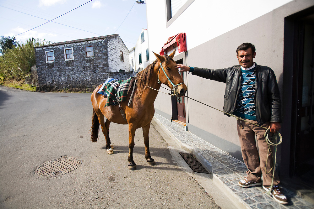 A man holds his horse outside of a cafe on the island of Faial. The Azores are a group of nine islands under Portuguese sovereignty. They mark the most westerly point of the E.U. and earn most of their income from agriculture and tourism.