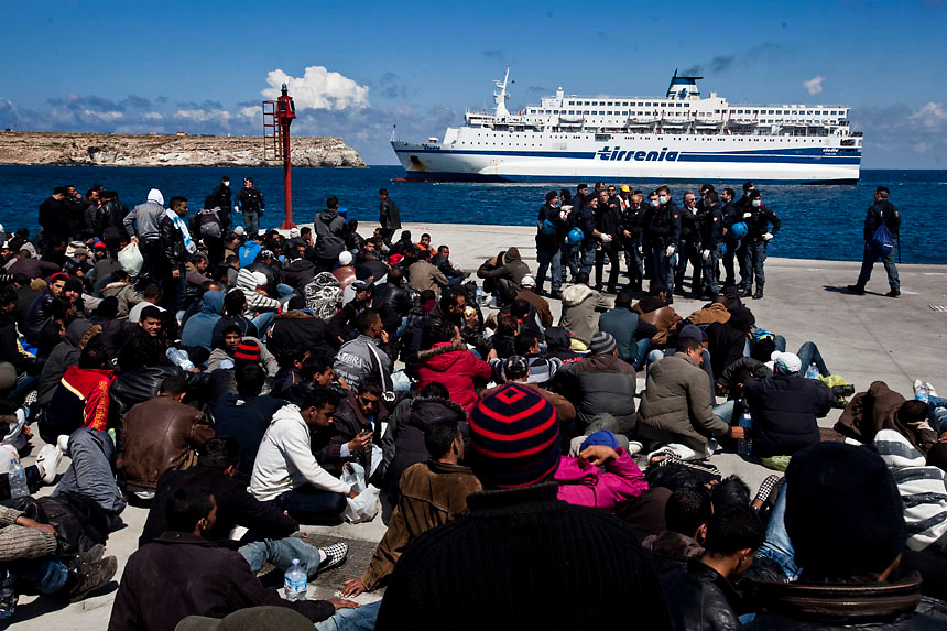 People fleeing unrest in Tunisia wait before boarding a cruise liner to a different part of Italy, on the southern island of Lampedusa . Italian Prime Minister Silvio Berlusconi promised to clear thousands of illegal Tunisian migrants from Lampedusa by the weekend after an outcry over a humanitarian crisis on the tiny southern island.