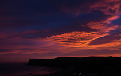 © Licensed to London News Pictures. 12/12/2013. Saltburn, UK. Sunrise lights up cloud formations over Huntcliff in Saltburn, Clevelend. Photo credit : Ian Forsyth/LNP