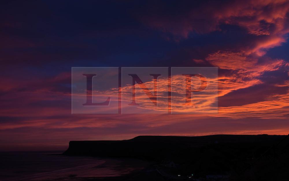 © Licensed to London News Pictures. 12/12/2013. Saltburn, UK. Sunrise lights up cloud formations over Huntcliff in Saltburn, Clevelend. Photo credit : Ian Forsyth/LNP